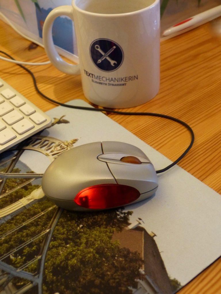Laptop-Maus auf Mauspad, weiße Tasse mit Textmechanikerin-Logo