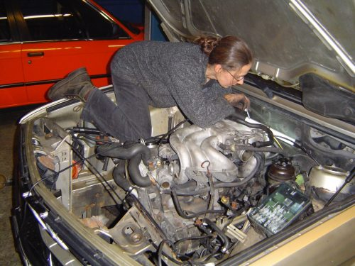 Im Motorraum eines BMW 525e: Textmechanikerin Elisabeth Strassert beim Schrauben statt Schreiben